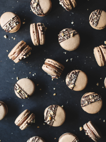 Macarons scattered on black background