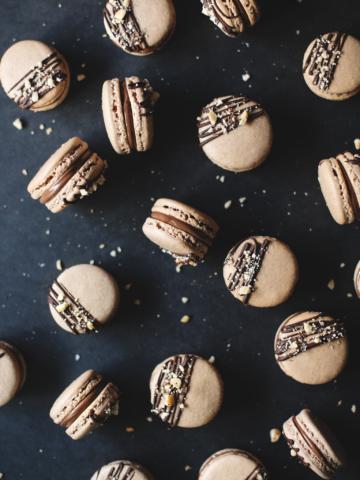 Macarons scattered on black background