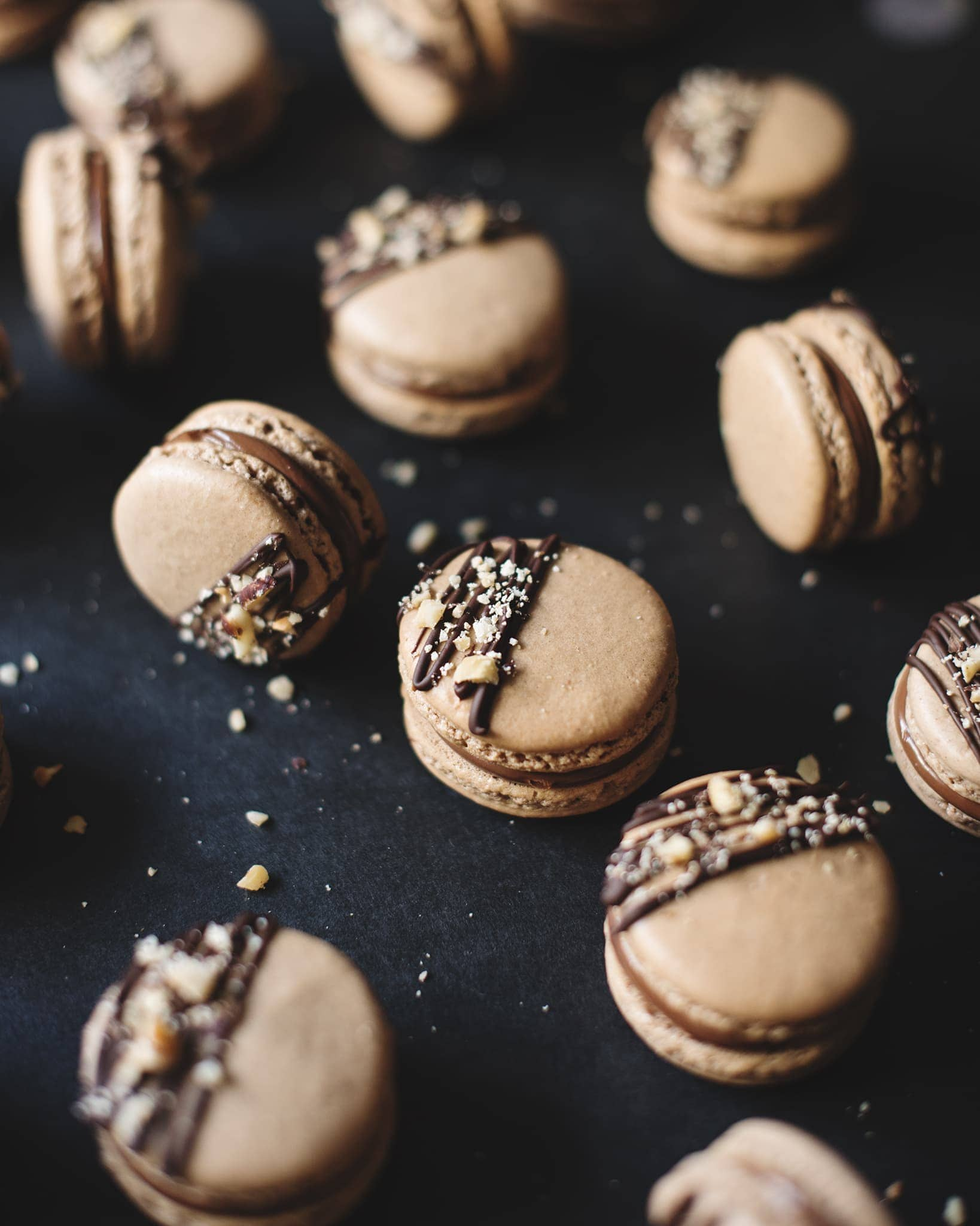 Ferrero Rocher macarons topped with dark chocolate drizzle and crushed hazelnuts scattered on a black background