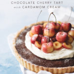 Chocolate cherry tart with cardamom cream on blue background