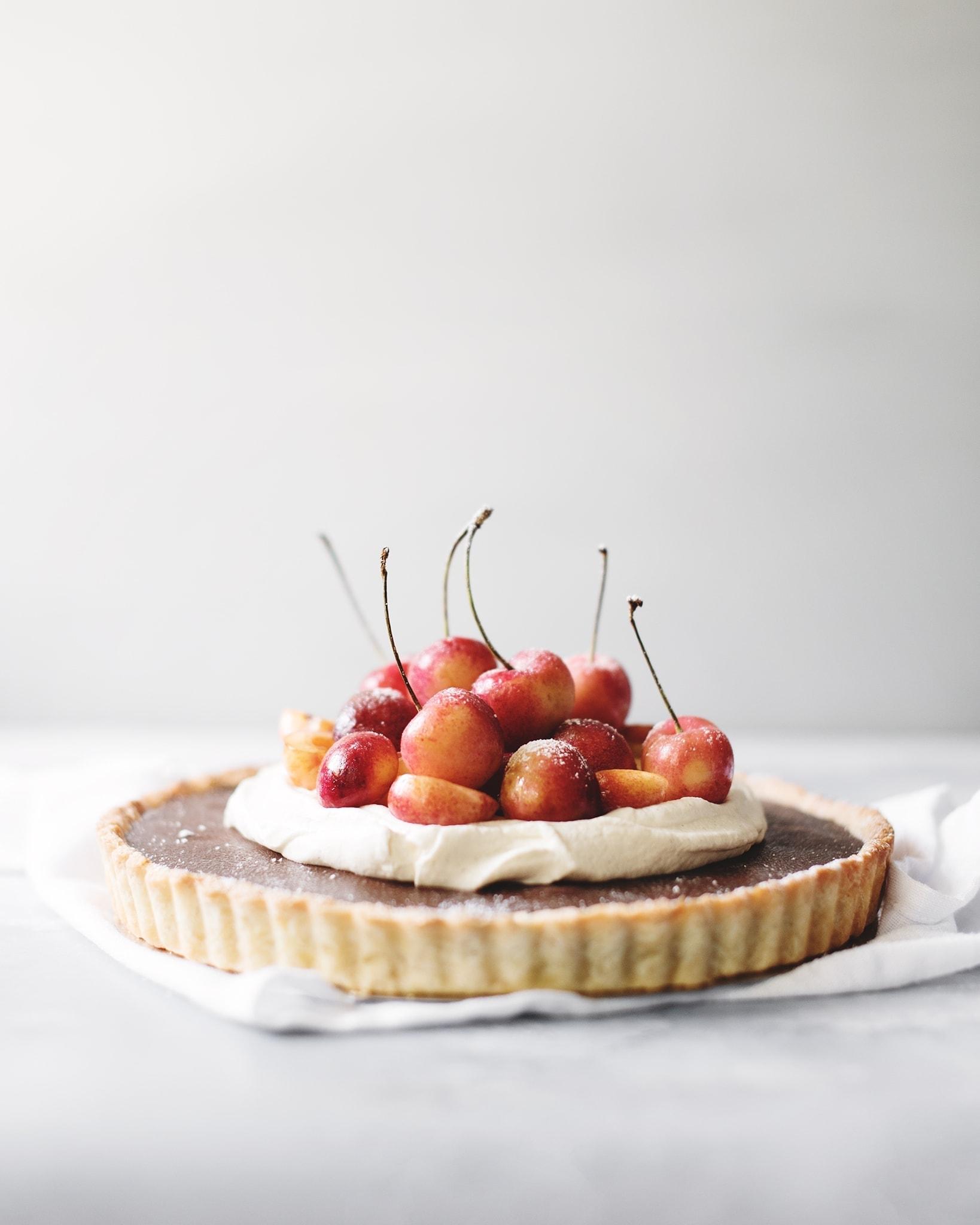 Rainier cherries on top of whipped cream and chocolate ganache tart on grey background