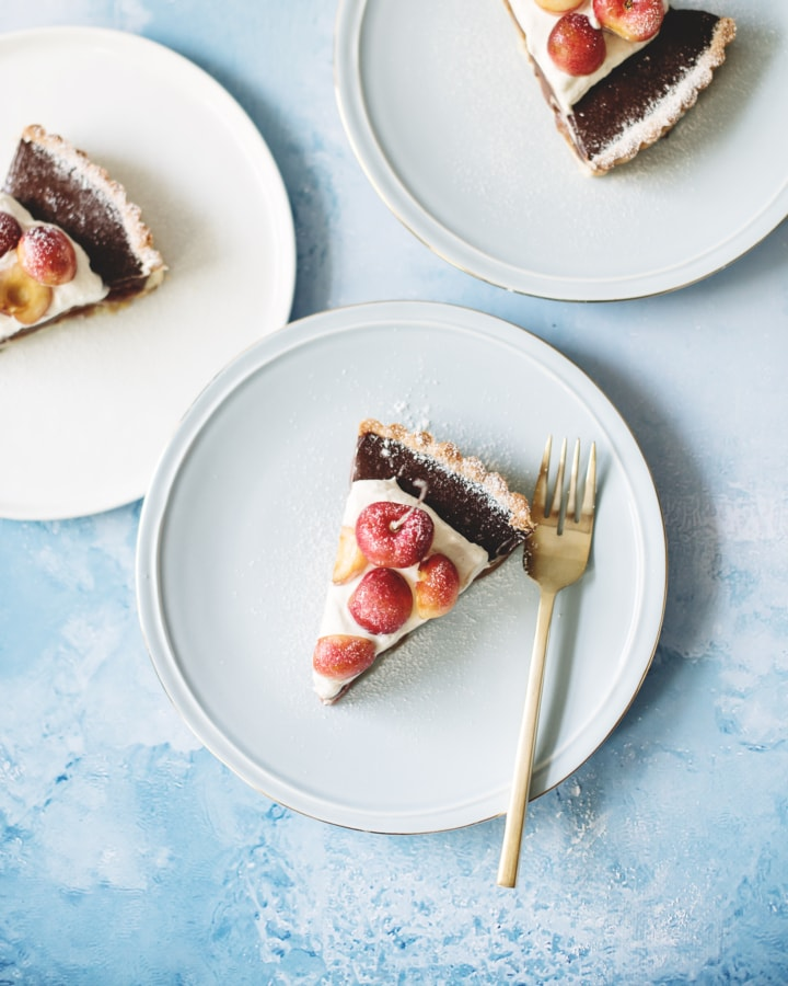 Overhead shot of slices of chocolate cherry tart with cardamom cream on blue plates and blue background
