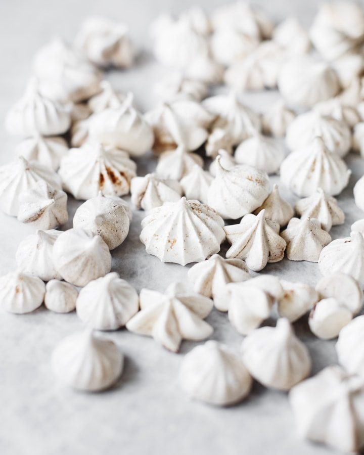 Many malted meringue kisses scattered on grey background