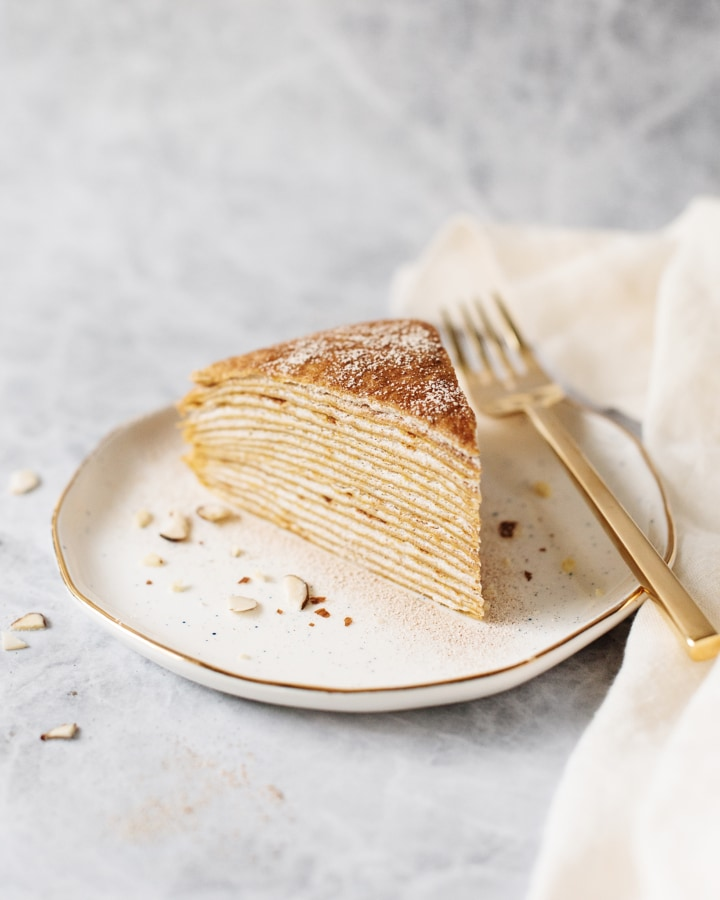A slice of pumpkin crepe cake on a white gold-rimmed plate with a gold fork