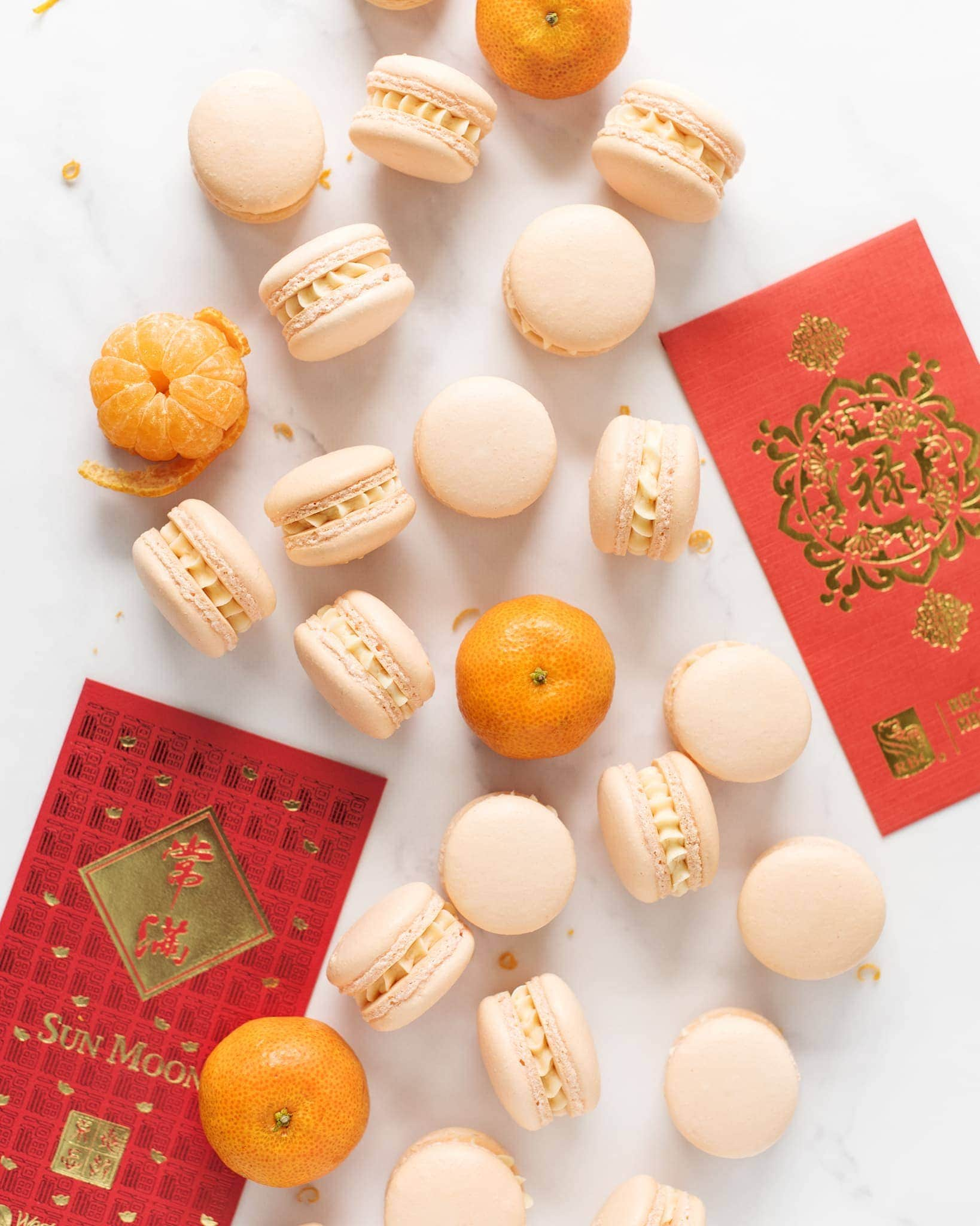 Mandarin orange macarons scattered on marble counter with Lunar New Year red envelopes