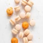 Mandarin orange macarons scattered on marble counter