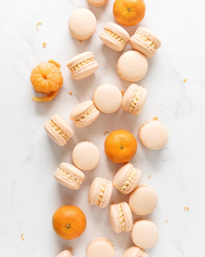 Mandarin orange macarons and mandarin oranges scattered on marble counter