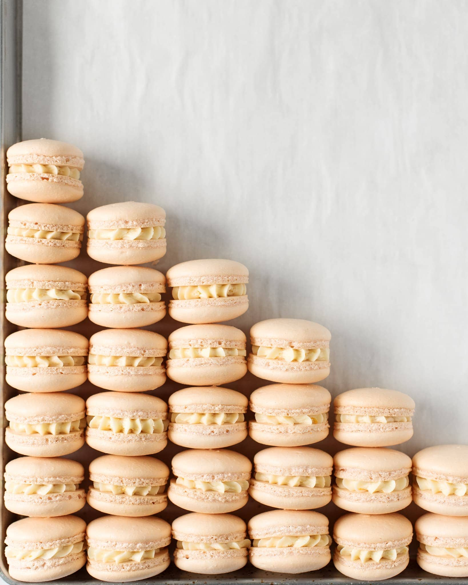 Mandarin orange macarons lined up in a triangle on a baking sheet