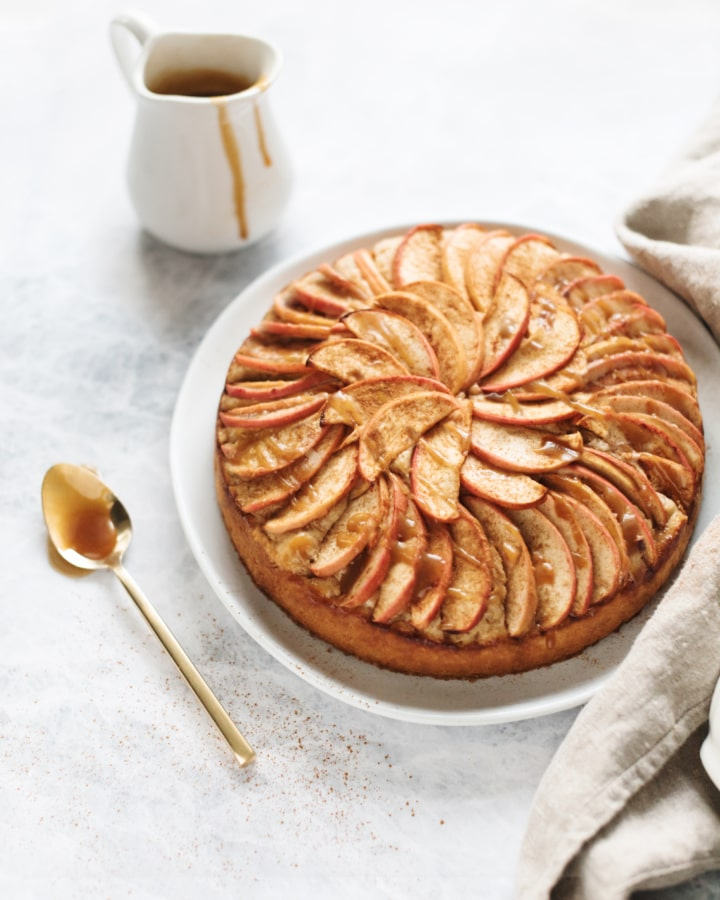 A spiced apple cake drizzled with salted maple caramel next to a spoonful of caramel
