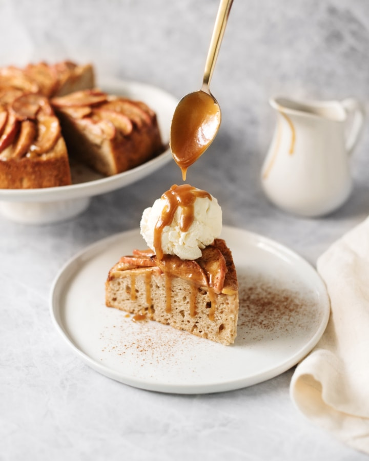 A slice of apple cake topped with a scoop of vanilla ice cream and drizzled with salted maple caramel from a spoon