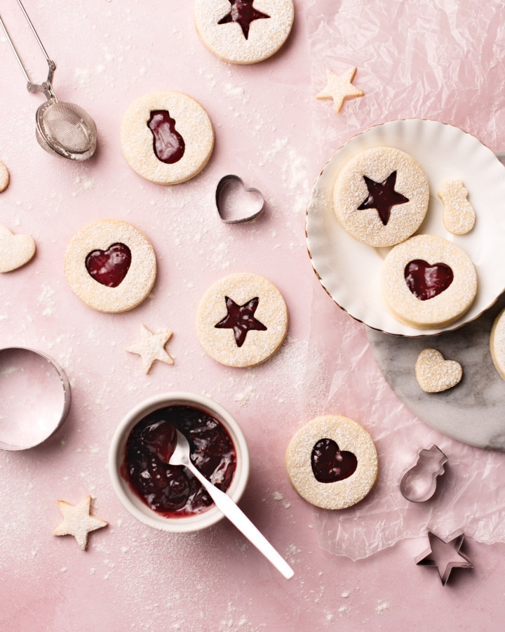 Raspberry rose linzer cookies with heart, star, and snowman cutouts on a pink background