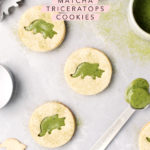 Matcha linzer cookies with triceratops cutouts on a grey background and sprinkled with matcha powder