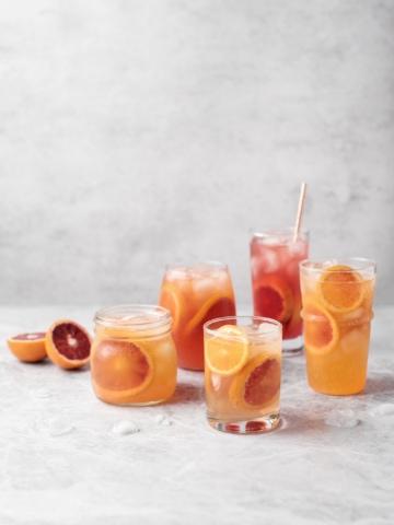 Glasses of blood orange paloma cocktails on grey background