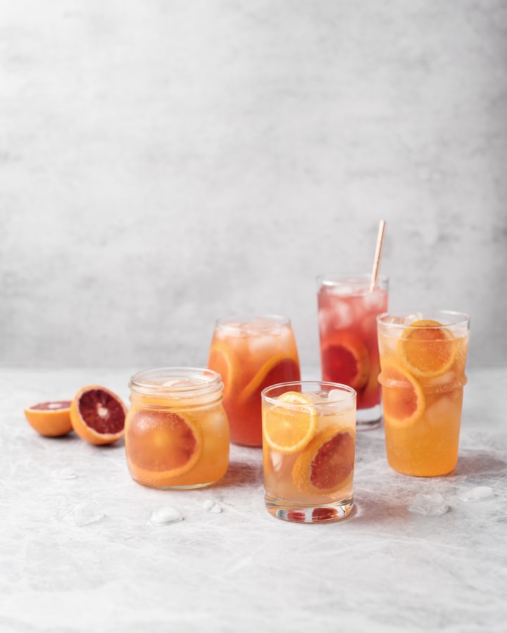 Glasses of blood orange paloma cocktails on grey background