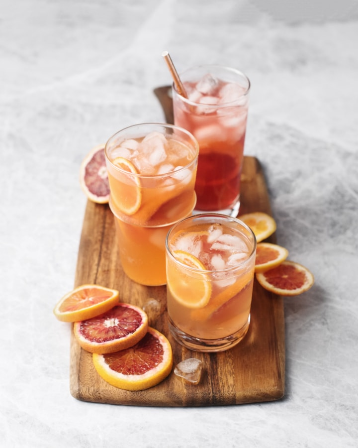 Glasses of blood orange palomas on a wooden serving board