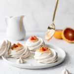 Spoonful of blood orange curd dripping into mini pavlovas
