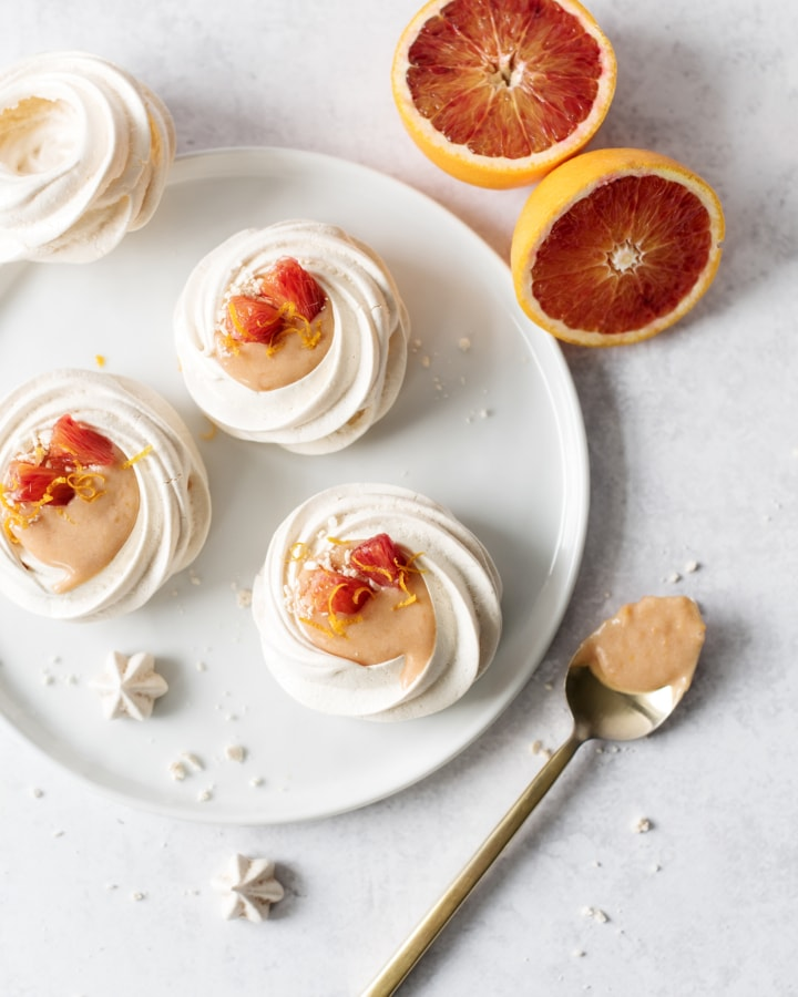 Overhead shot of a plate of blood orange curd pavlovas