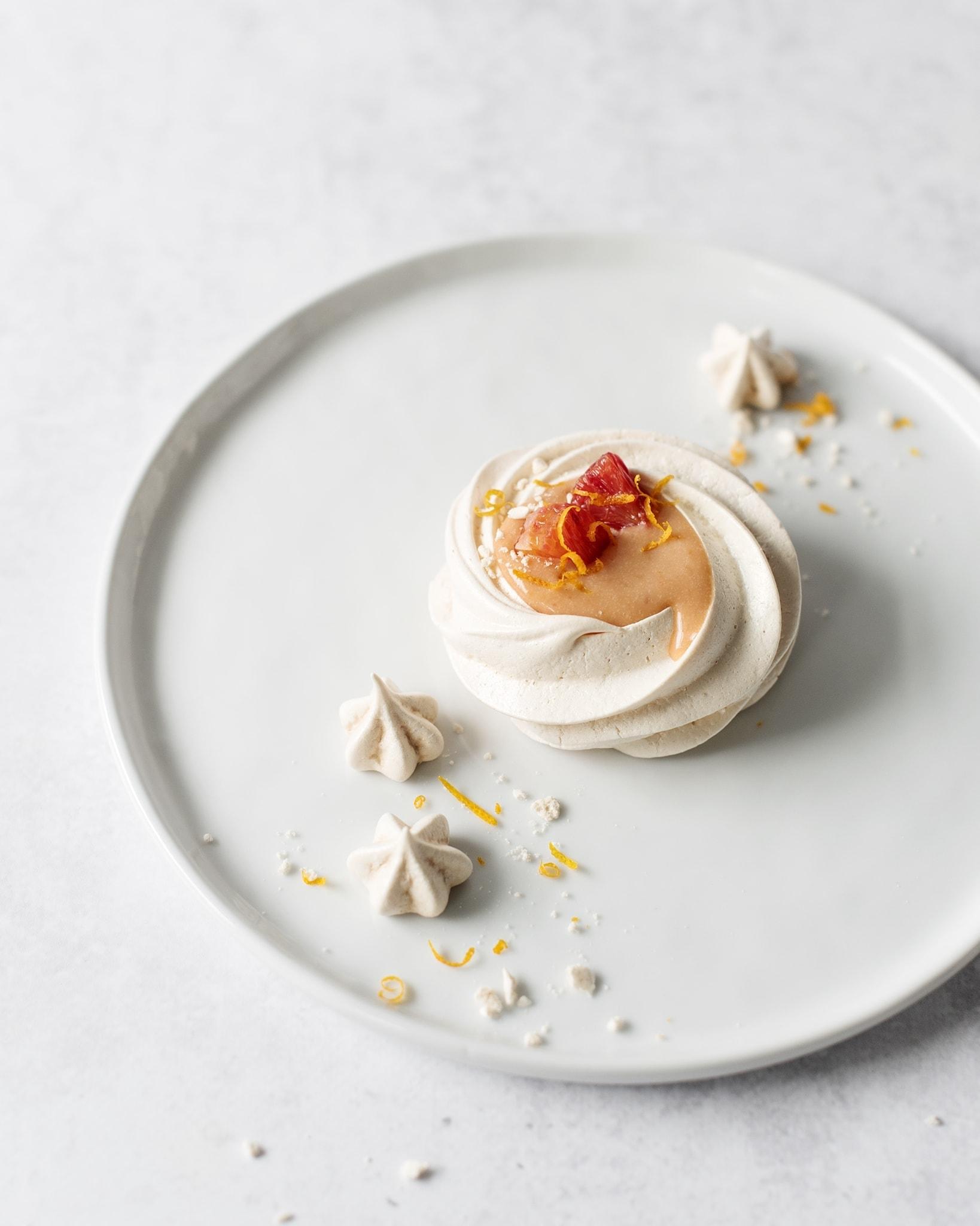 One blood orange pavlova on a white plate with mini meringues