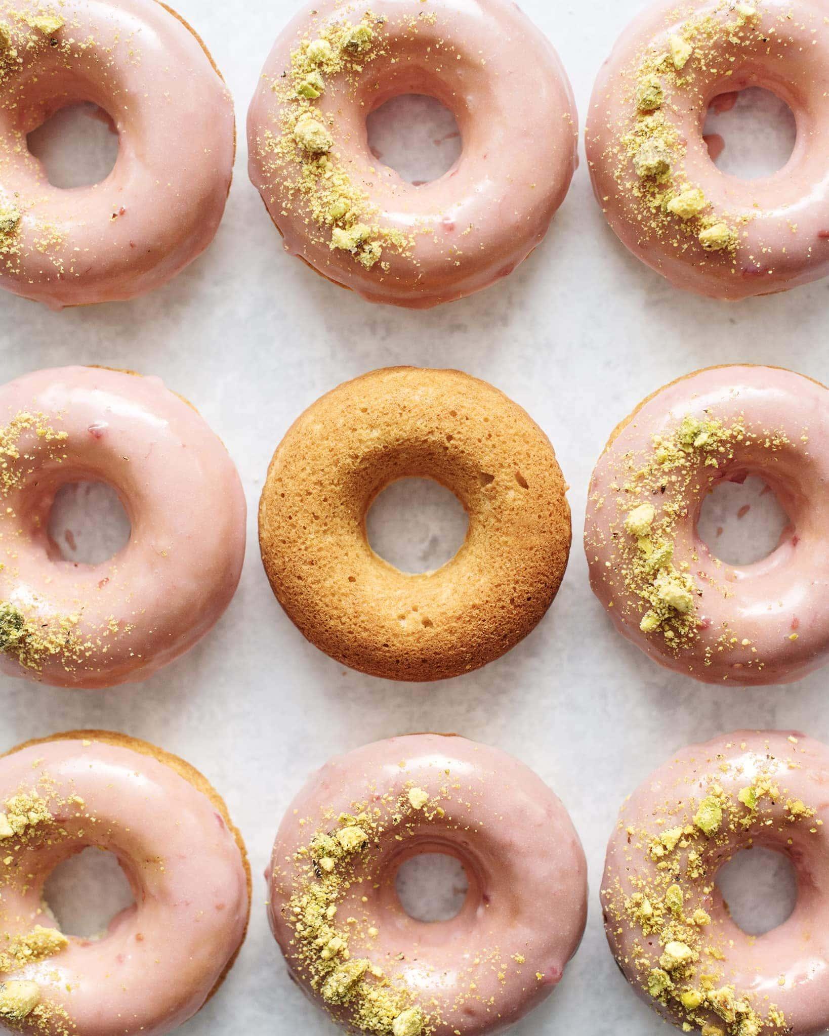 One unglazed donut surrounded by glazed raspberry pistachio donuts
