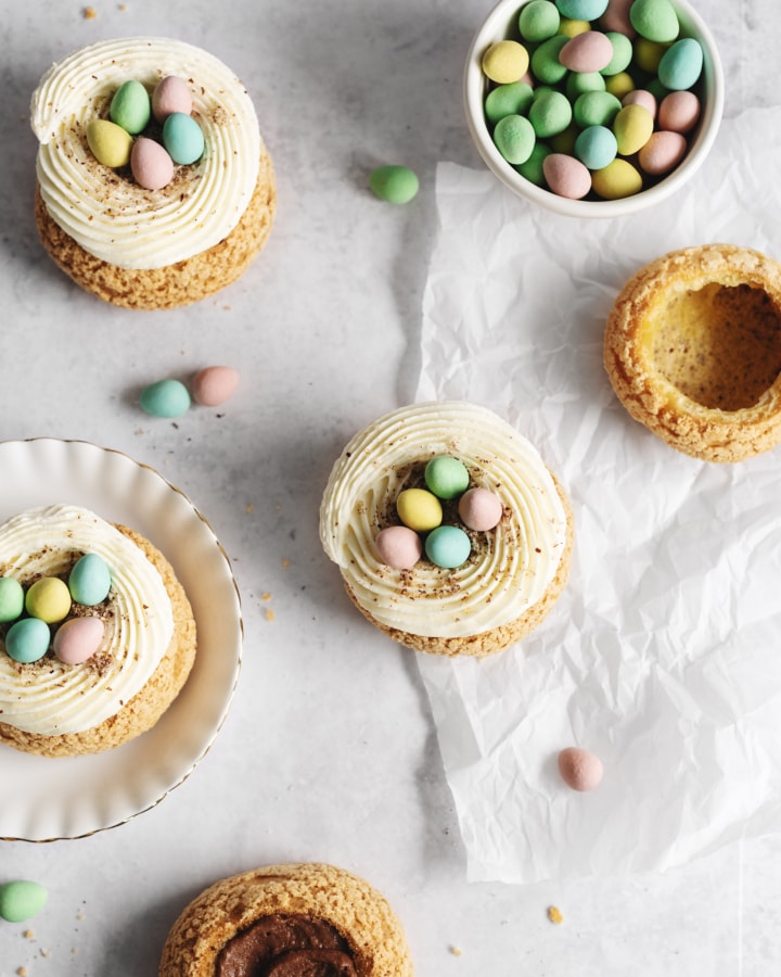 Overhead shot of cream puffs on parchment with a bowl of mini eggs