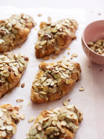 Almond croissants sprinkled with sliced almonds on pink background