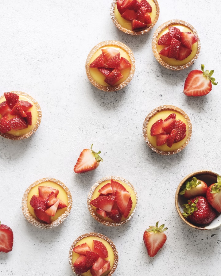 Overhead shot of lemon curd tartlets scattered on grey background with strawberries