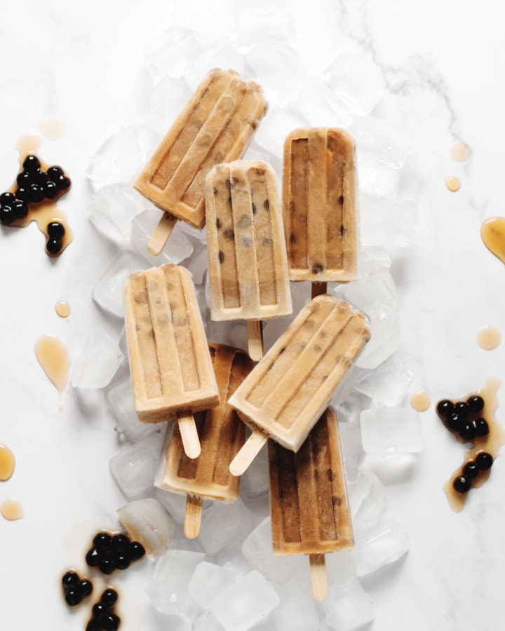 Several boba milk tea popsicles on top of ice cubes