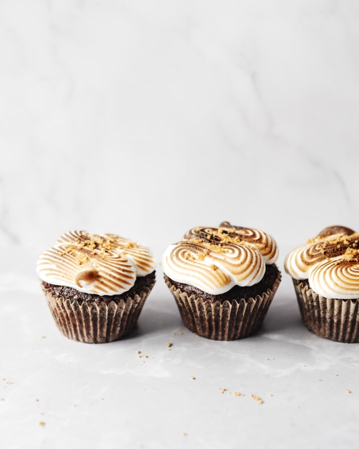 Two s'mores cupcakes on grey background