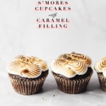 Two s'mores cupcakes on grey background with text overlay