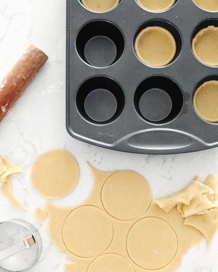 Circles of tart dough placed in muffin pan