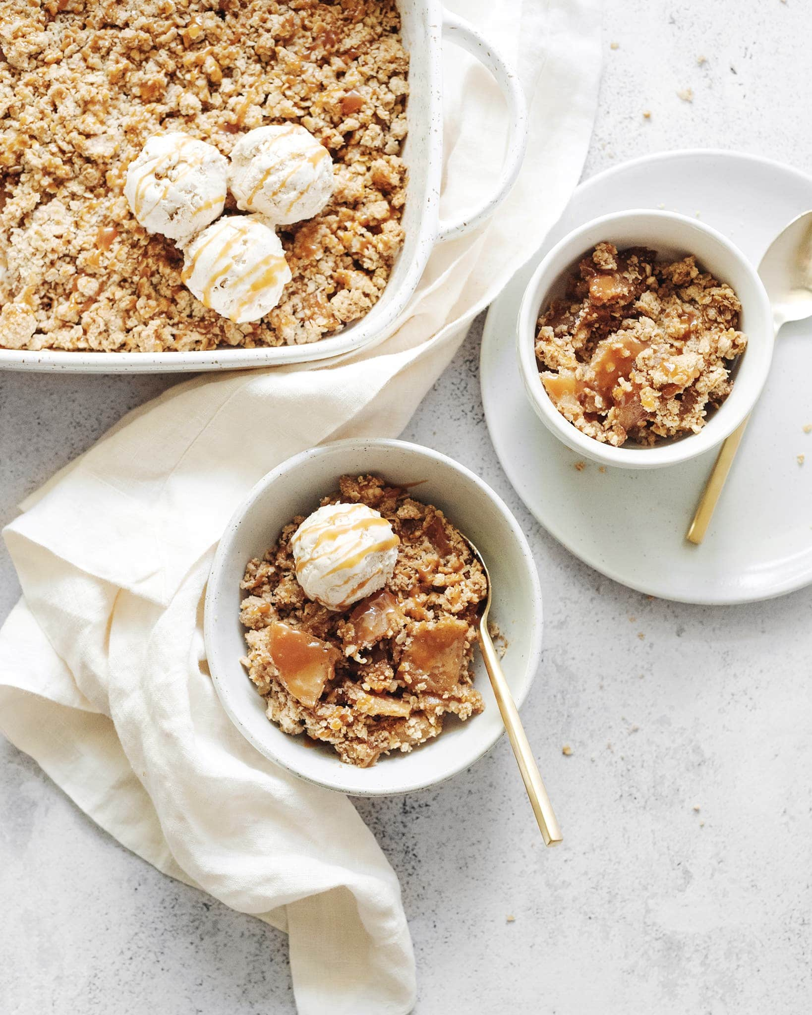 A baking dish and bowls of caramel apple crisp topped with ice cream