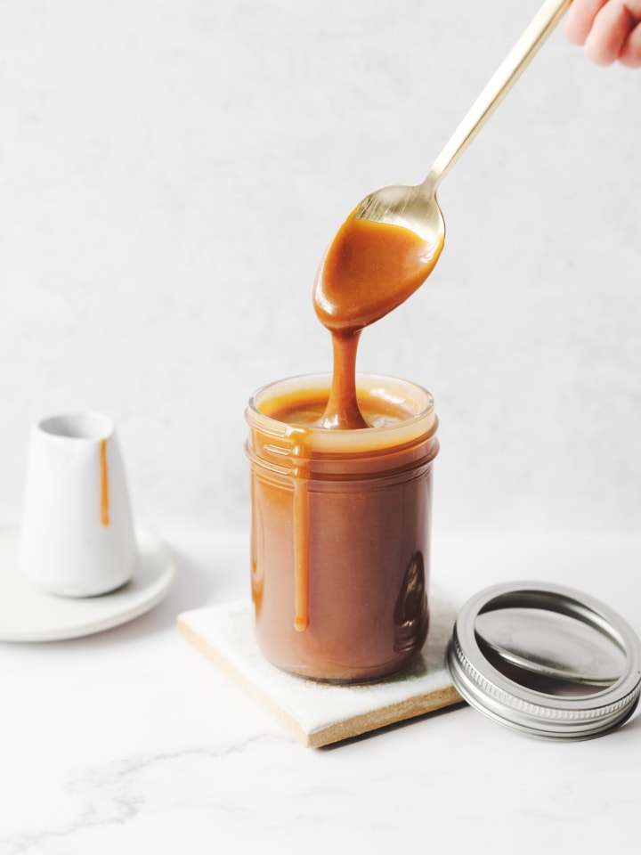 Spoon dripping with caramel sauce above glass jar