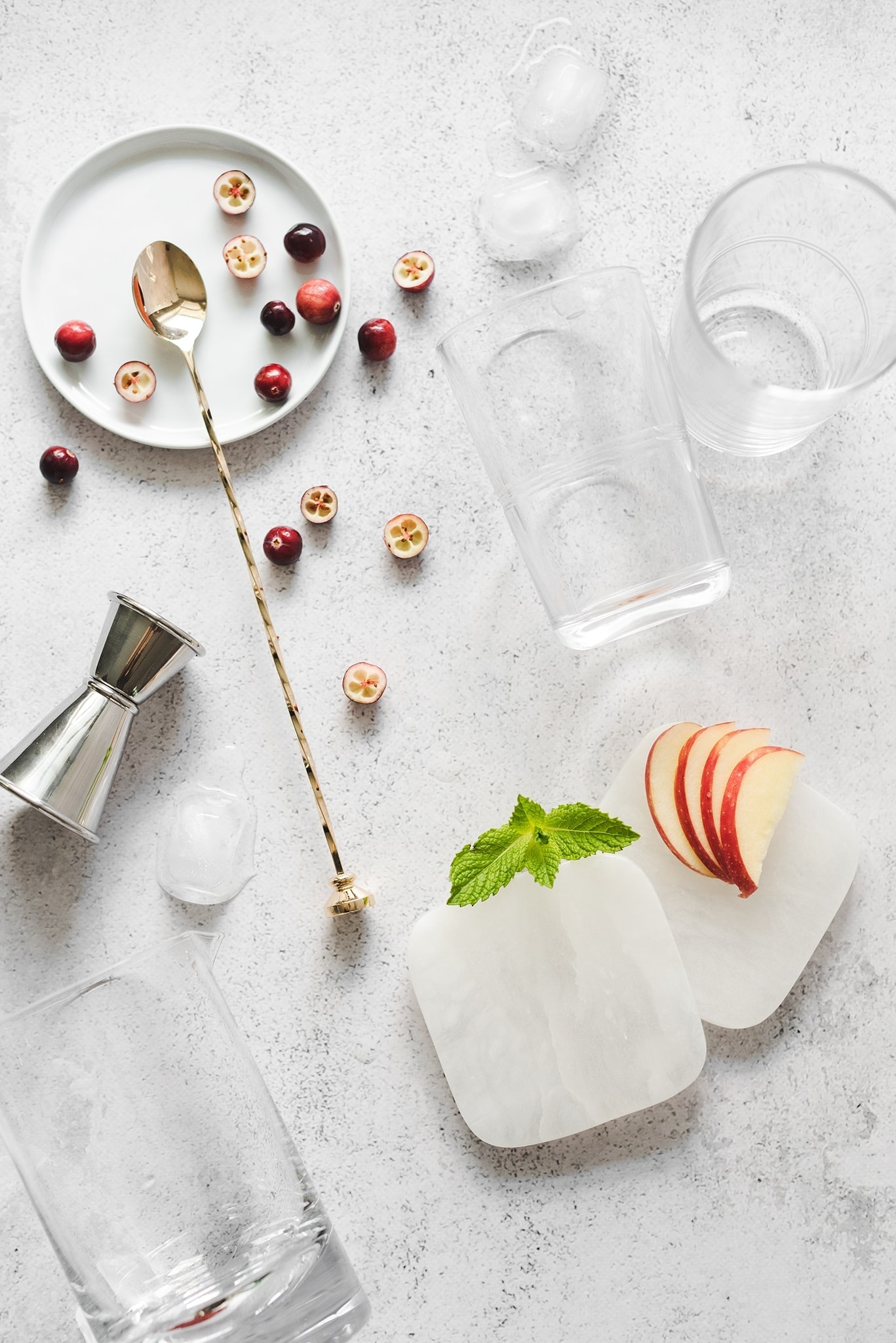 Glasses, coasters, and ingredients for cranberry apple mojitos