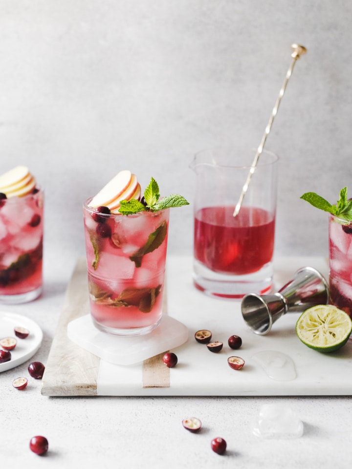 Cranberry apple mojitos on a marble and wood serving tray