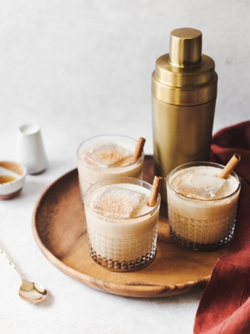 Pumpkin spice white russian cocktails and gold cocktail shaker on wood platter