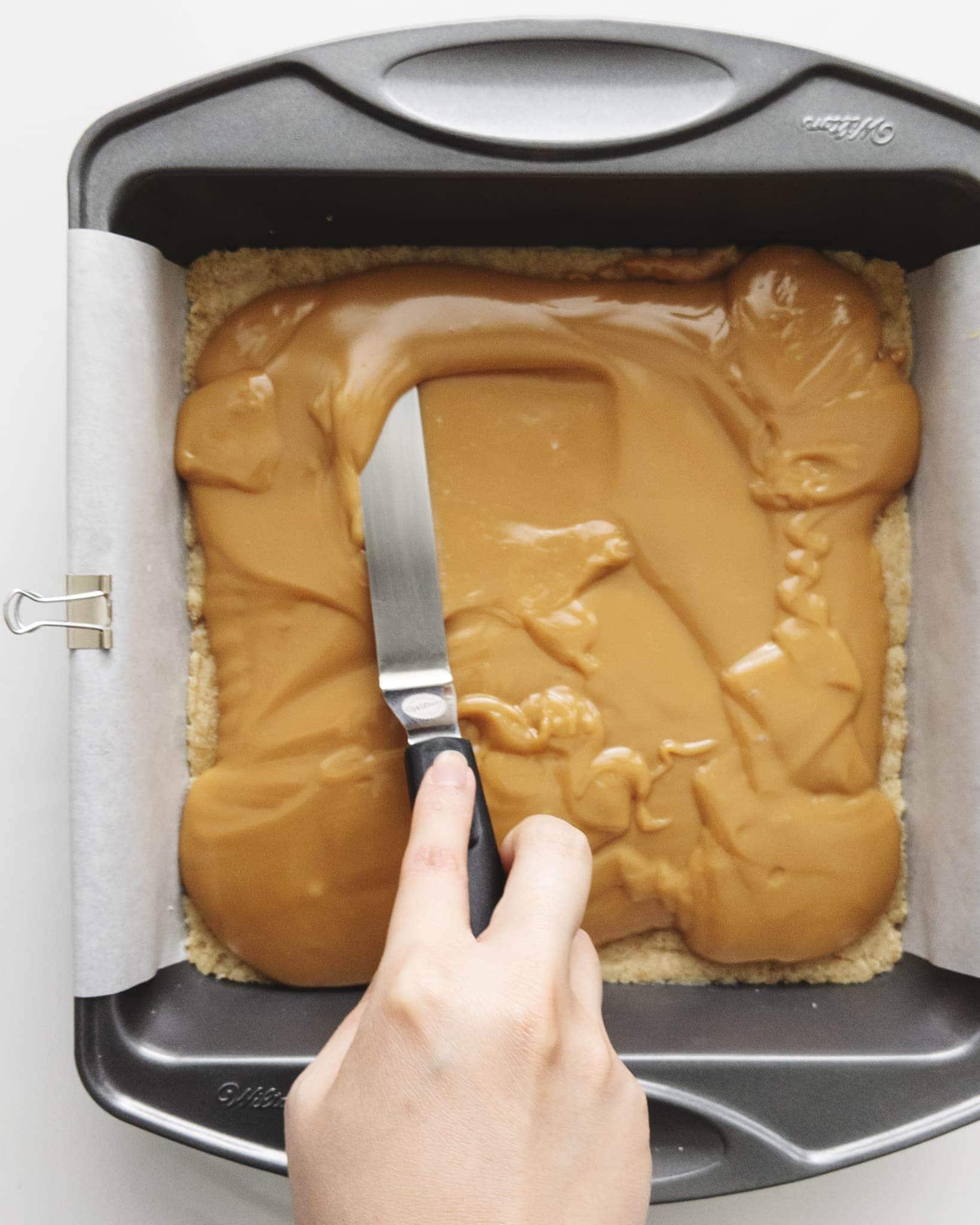 Spreading caramel across shortbread base