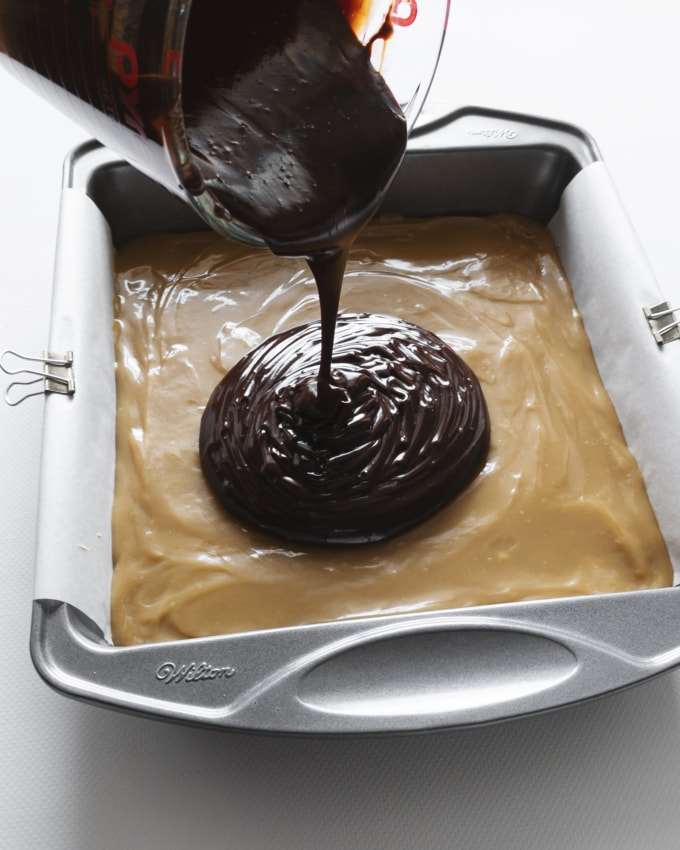 Pouring chocolate ganache on top of caramel layer