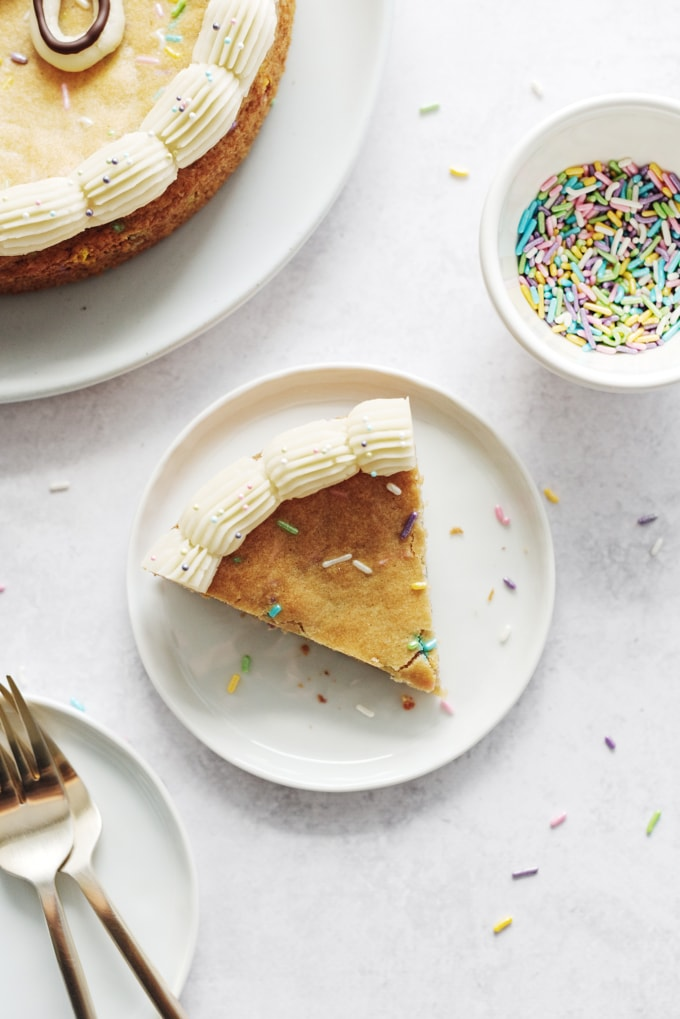 A slice of cake on a plate with sprinkles