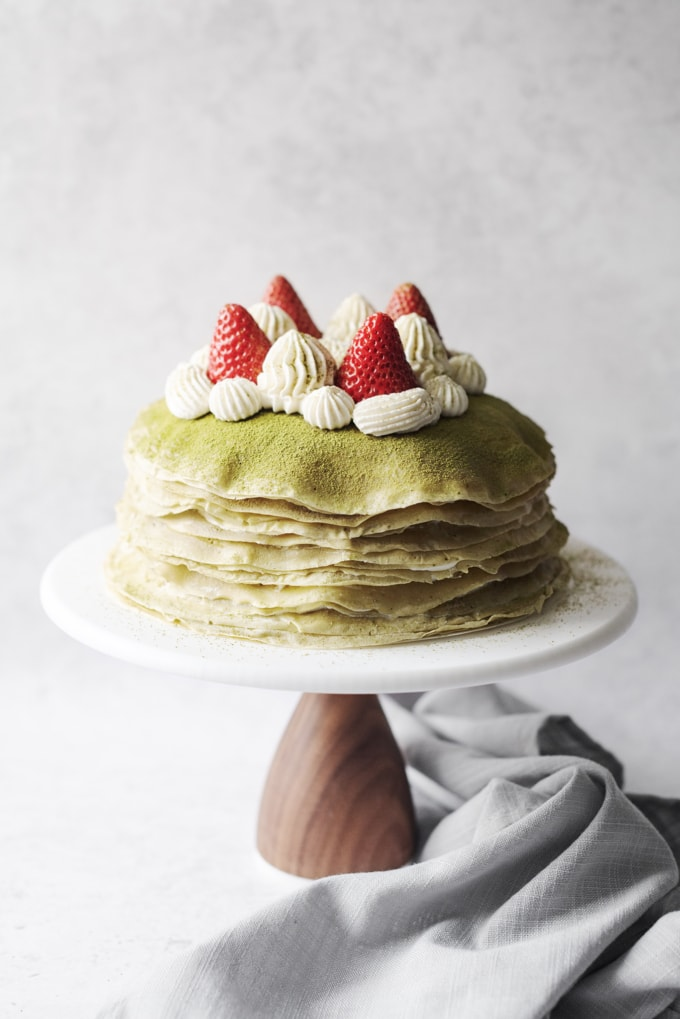 Crepe cake topped with strawberries and whipped cream