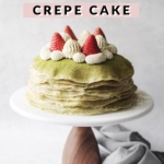 Crepe cake on cake stand topped with strawberries and whipped cream