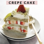 A slice of crepe cake on a plate with gold fork
