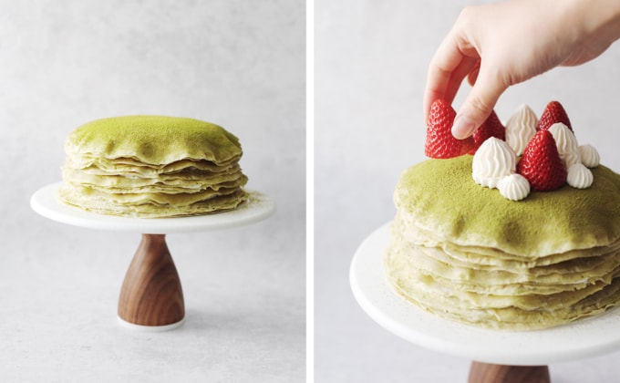 Hand placing strawberry on top of crepe cake