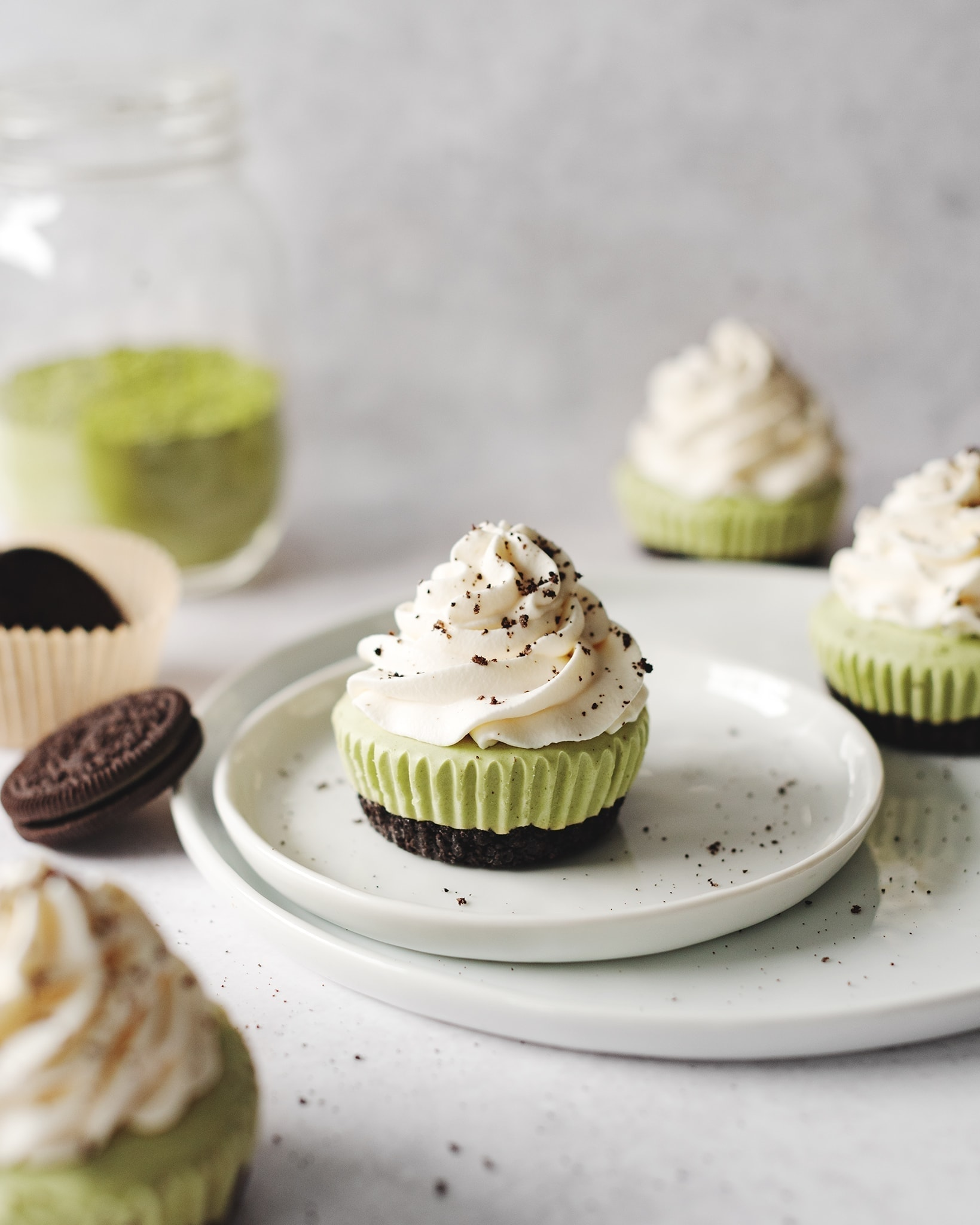 Matcha cheesecakes topped with whipped cream on plate with oreos