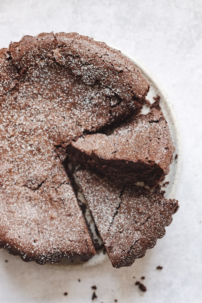 Slices cut out of a chocolate cake dusted with powdered sugar