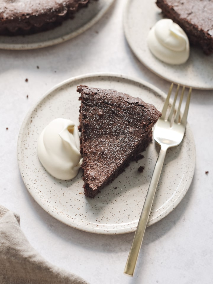 A slice of flourless chocolate cake on a plate with whipped cream