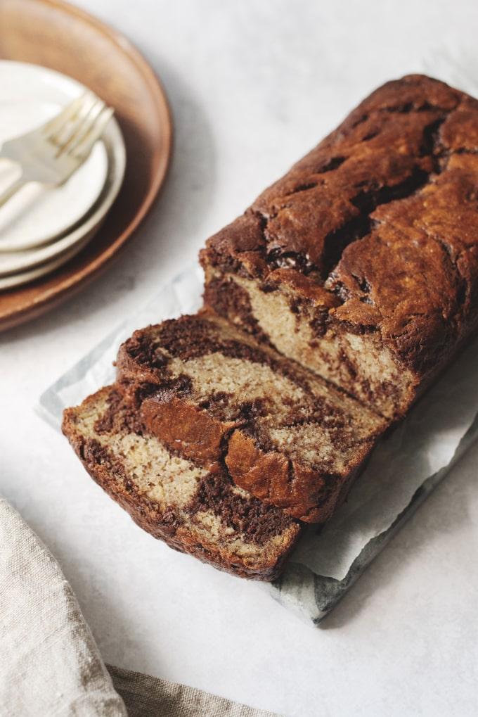 Slicing chocolate swirl banana bread form the loaf
