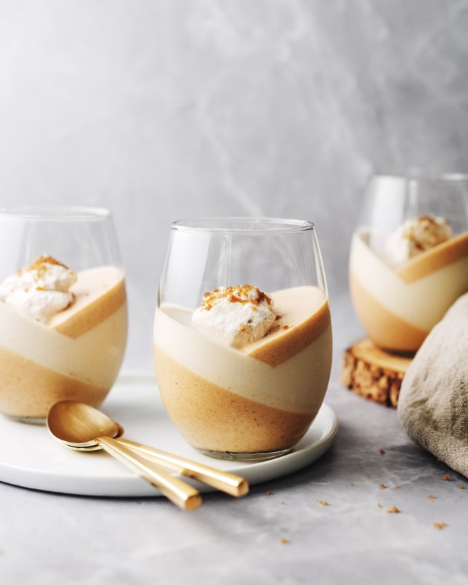 Pumpkin panna cotta topped with whipped cream in a glass
