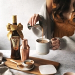 Pouring Amarula cream liqueur into a mug of hot chocolate and coffee