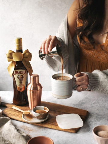 Pouring Amarula cream liqueur into a mug of hot chocolate and coffee
