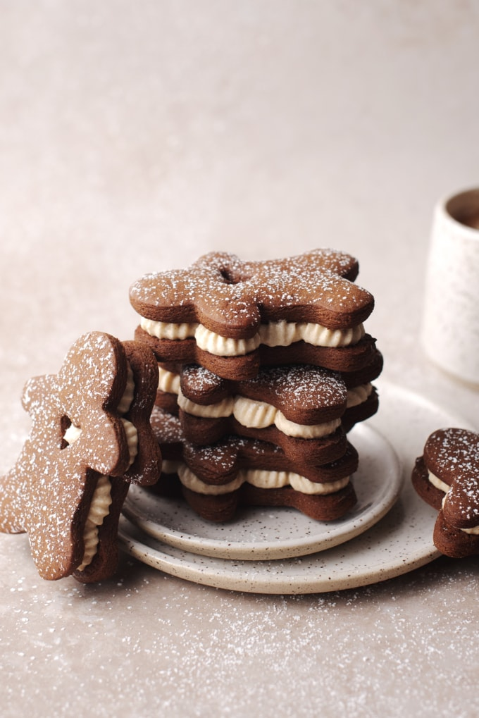 Stack of gingerbread sandwich cookies with ginger cream filling on plate